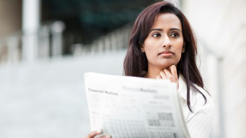 Indian businesswoman reading newspaper outdoors. (Take A Pix Media)